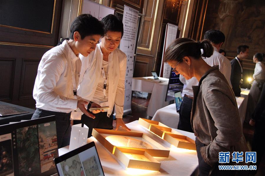8月20日,在丹麦首都哥本哈根,中国设计师与参观者交谈.