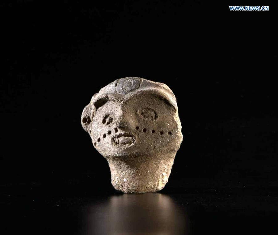 Mysterious female pottery face sends 7,300 year-old smile