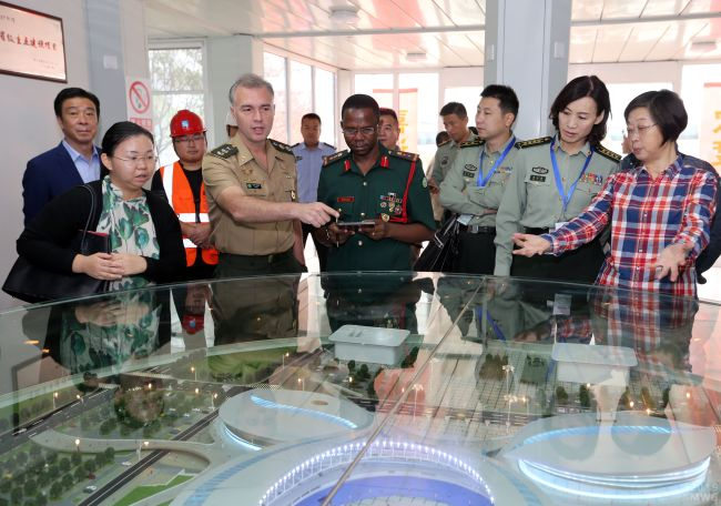 Officials of the International Military Sports Council (CISM) stand in front of a sand table during a visit to the Dongxihu Sports Center on October 9, 2018 to inspect the progress of the project. [Photo: Changjiang Daily]