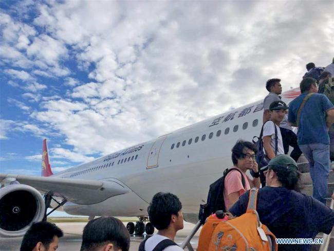 Chinese tourists get on board to fly back home in Saipan, the Commonwealth of the Northern Mariana Islands (CNMI), Oct. 28, 2018. Some 1,500 Chinese tourists trapped in Saipan by Super Typhoon Yutu started to fly back home on Sunday. [Photo: Xinhua]