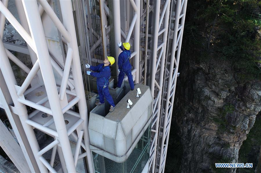 Mechanic conducts routine checks to guarantee cliffside elevator's safe operation