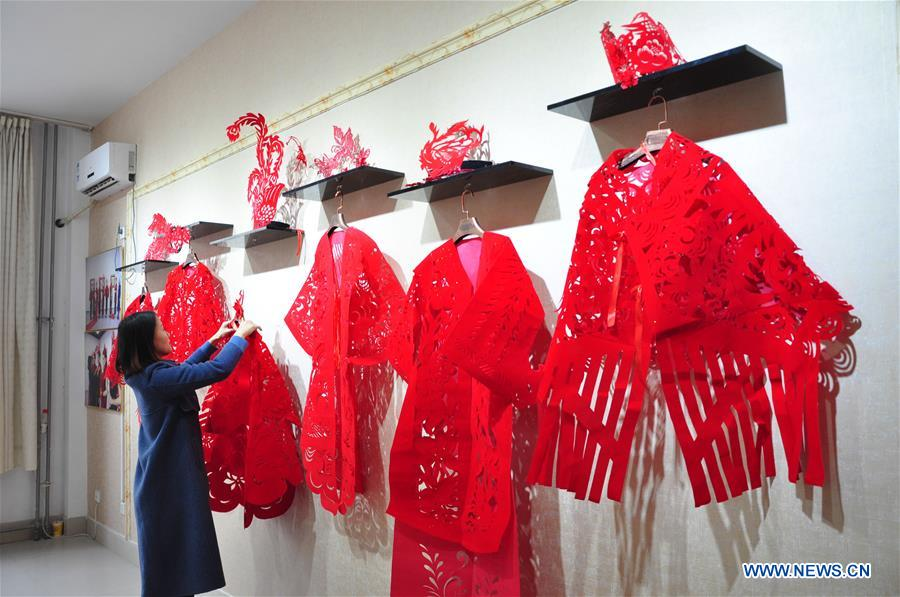 Pic story: craftswoman makes papercutting works of cheongsam to greet Spring Festival