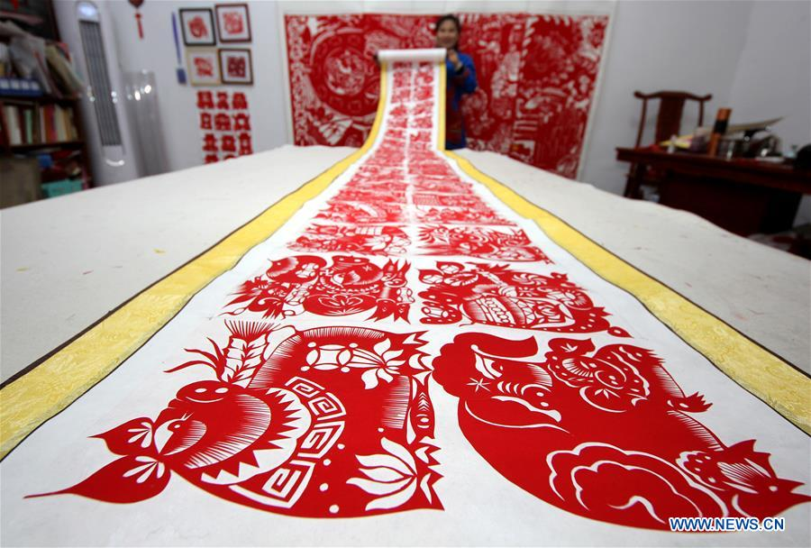 Folk artist makes pig-themed paper cutting artwork to greet Year of Pig in China's Shandong