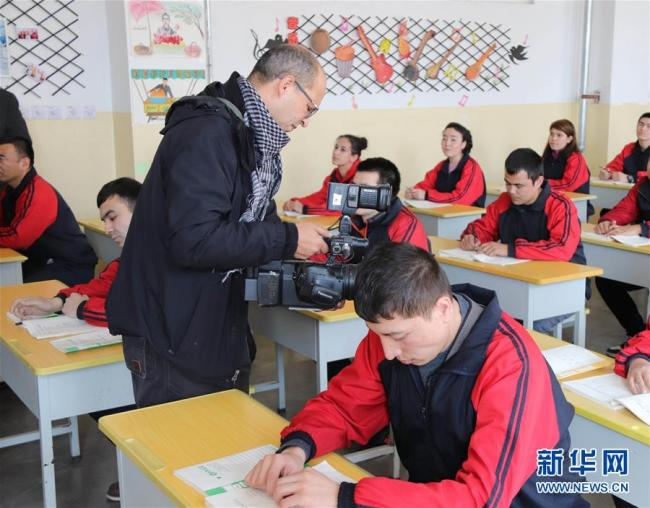 Hamdi Emam, a cameraman for Nile TV, is shooting students studying at Kashgar Vocational Training Center. [Photo: Xinhua]