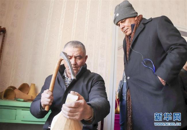 Kamal Gaballa, a columnist with Al-Ahram newspaper, watches Rehman Abdulla making a traditional music instrument called dutar in a village of Shufu County. [Photo: Xinhua]