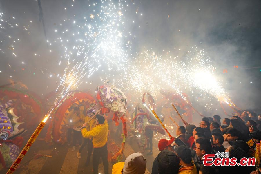 People perform dragon dance with a background of firecrackers in Yuqing County, southwest China\'s Guizhou Province, Feb. 16, 2019. Villagers gathered and performed dragon dances to celebrate the upcoming Lantern Festival,which falls on Feb. 19 this year.