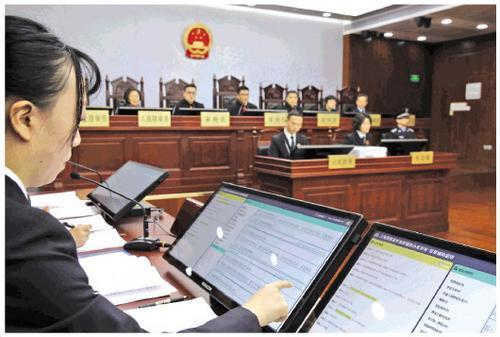A public prosecutor reviews evidence presented by the AI system during a hearing at a Shanghai court on Wednesday, January 23, 2019. [File photo: Legal Daily]