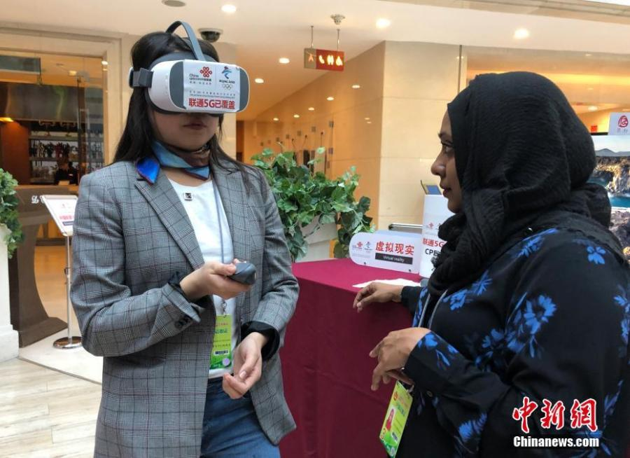 Mongolian journalist Enkhtur Anudari (L) experiences a 5G network device at the media center of the Two Sessions in Beijing\'s Media Center Hotel, March 11, 2019. (Photo: Cui Nan/China News Service)