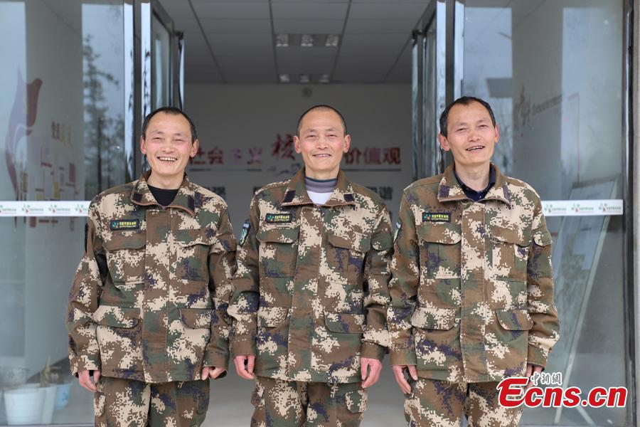 Triplet brothers Zhang Jian (front), Zhang Zhong (center), and Zhang Hua pose for a photo in front of their office building in Bijie City, Guizhou Province, March 10, 2019. Influenced by their father, the three brothers began to work as rangers in the farm in 1981. The tree farm covers an area of 53,300 mu (3,553 hectares) and the brothers usually walk approximately 30 kilometers on average per working day. Guizhou has about 3,000 registered rangers who work in tree farms totalling 5.55 million mu. (Photo: China News Service/Qu Honglun)