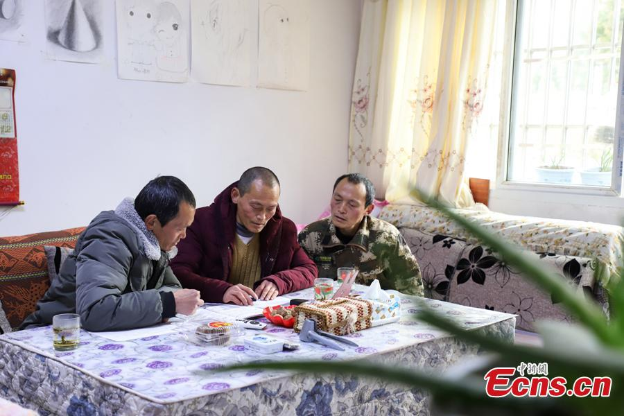 Triplet brothers Zhang Hua (L), Zhang Jian, and Zhang Zhong prepare an inspection report in the Gonglongping state-owned tree farm in Bijie City, Guizhou Province, March 10, 2019. Influenced by their father, the three brothers began to work as rangers in the farm in 1981. The tree farm covers an area of 53,300 mu (3,553 hectares) and the brothers usually walk approximately 30 kilometers on average per working day. Guizhou has about 3,000 registered rangers who work in tree farms totalling 5.55 million mu. (Photo: China News Service/Qu Honglun)