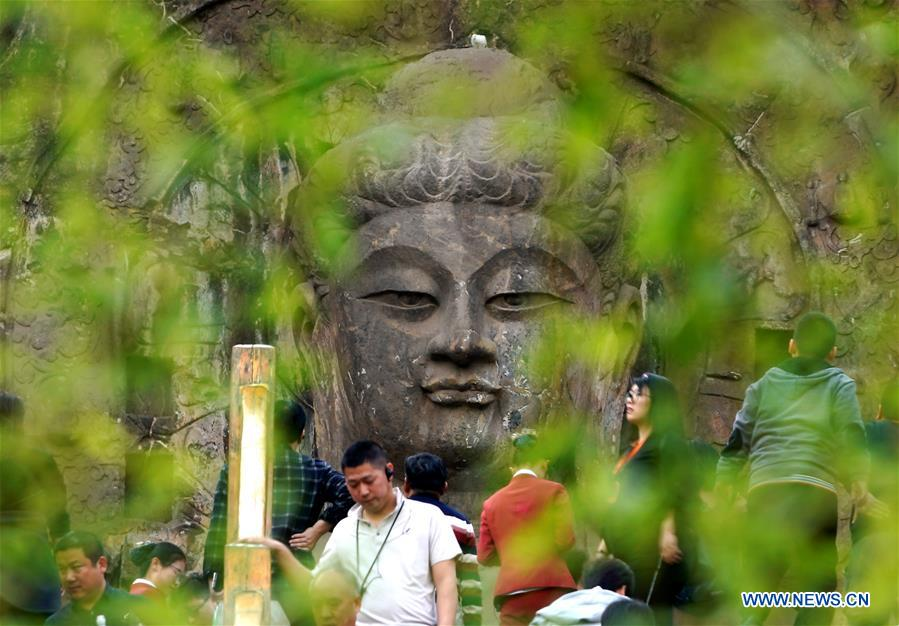 People visit Longmen Grottoes scenic area in Luoyang, C China's Henan