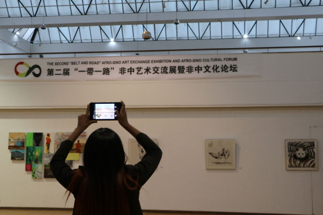 A visitor takes a picture of the art works displayed at the Second Belt and Road Afro-Sino Art Exhibition. The exhibition is launched the National Gallery of Zimbabwe on Monday, April 29, 2019. [Photo: China Plus/Gao Junya]