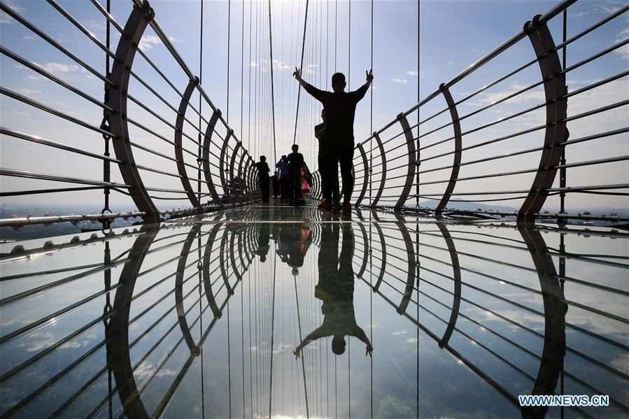 Tourists walk on a glass bridge at the Huaxi World Adventure Park in Huaxi Village of Jiangyin City, east China\'s Jiangsu Province, May 4, 2019. The 518-meter-long glass bridge hangs more than 100 meters above ground level at the park. It is made of panes of 35-mm-thick glass. Each glass can hold a maximum weight of 4.7 tonnes. Around 2,600 people can cross the bridge at a time. (Xinhua/Xu Congjun)