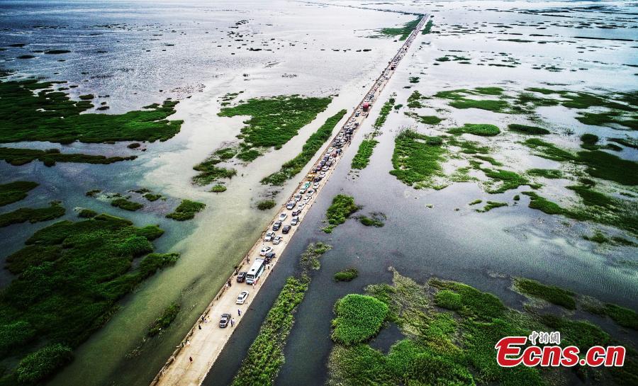 Photo taken on June 16, 2019 shows the submerged Dahuchi section of Yongxiu-Wucheng Road in East China\'s Jiangxi province. Continuous rain in Jiangxi has led to a rise of water level of the Poyang Lake, China\'s largest freshwater lake. The Dahuchi section of Yongxiu-Wucheng Road was submerged in water. (Photo: China News Service/Mao Jiajia)